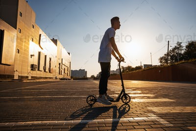 Young guy dressed in jeans and t-shirt is riding a scooter on the square paved with tiles near the