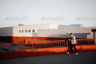 Young stylish guy dressed in jeans and white t-shirt is walking next to the urban building with