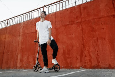 Young guy dressed in jeans and t-shirt stands with a scooter against a painted concrete wall on the