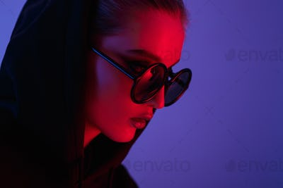 Portrait of fashion young girl in a black sweater with a hood and round sunglasses in red and blue