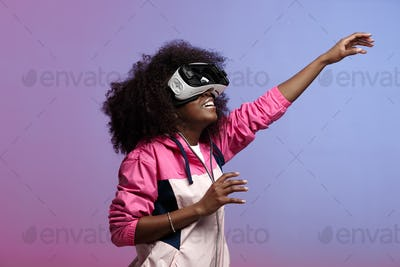 Modern curly brown-haired girl dressed in the pink sports jacket uses the virtual reality glasses in