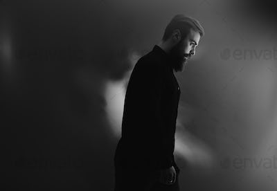 Black and white photo of a stylish man with a beard dressed in the black shirt stands in profile in