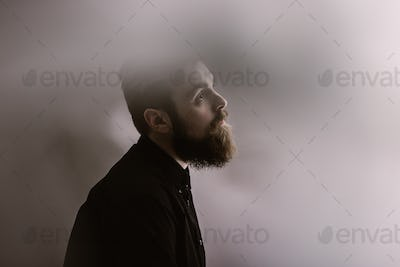 Sepia photo portrait of a stylish man in profile with a beard dressed in the black shirt in the fog
