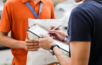 A person wearing an orange T-shirt and a name tag is delivering a parcel to a client, who is putting
