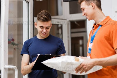 A person wearing an orange T-shirt is delivering a parcel to a satisfied client, who is putting his