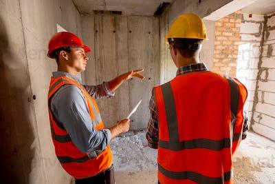 Two civil engineers dressed in orange work vests and helmets walk inside the building under