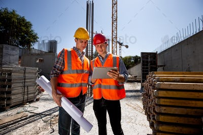 Civil architect and construction manager dressed in orange work vests and helmets discuss a building
