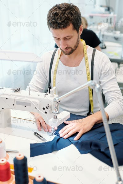 Young serious tailor concentrating on sewing work while sitting by machine