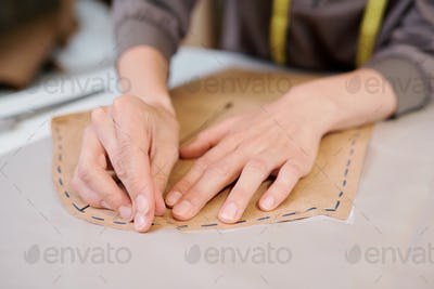Young female tailor pinning paper workpiece to piece of fabric