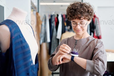 Young tailor taking pin from pincushion on her wrist during work