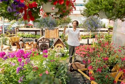 Contemporary florist or gardener walking through garden center
