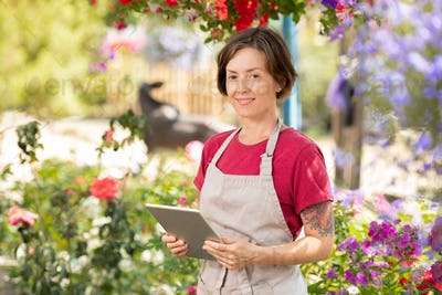 Happy female gardener with touchpad working over online price list