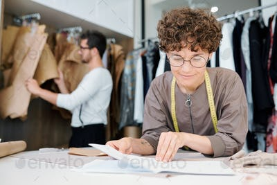 Young female seamstress or fashion designer looking at sketch of new model