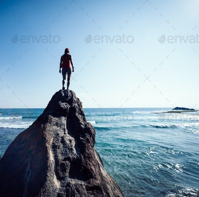 Strong woman walking to the cliff edge on seaside for solution