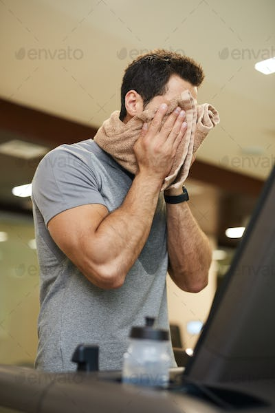 Man Wiping Sweat in Workout