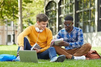 Two College Students Sitting on Grass