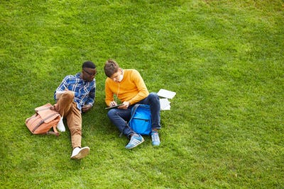 Two Students Relaxing on Green Grass
