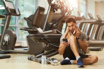 Man Sitting on Floor in Gym