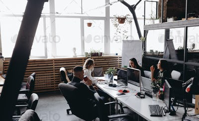 Young team works in a spacious light modern open space office sitting at a desks with a computer and