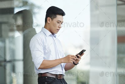 Young entrepreneur checking phone