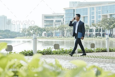 Businessman walking and talking on phone