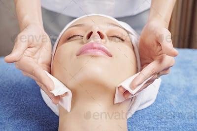 Beautician applying toner