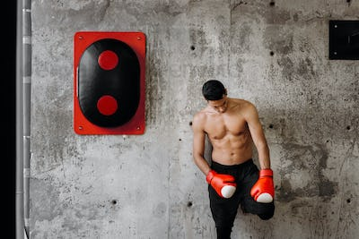 Brutal dark-haired guy with a naked torso and the red boxing gloves stands against a concrete wall