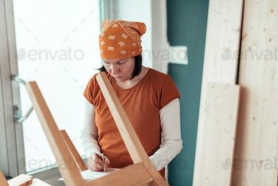 Female carpenter repairing wooden chair seat in workshop