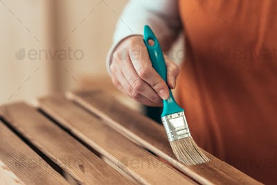 Female carpenter varnishing wooden crate with brush