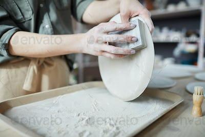 Female Ceramist Sanding Plates