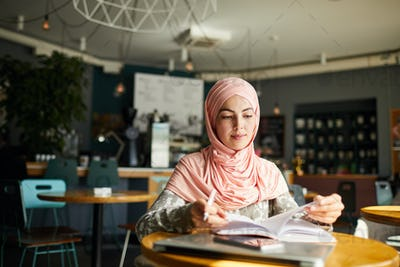 Muslim woman reading in cafe