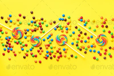 Multicolored lollipop, rainbow colorful candies on yellow background. Coated chocolate sweet pieces