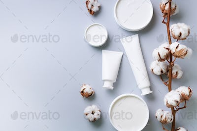 Fluffy cotton flowers, face cream, body butter on grey background with copy space. Cosmetics, beauty