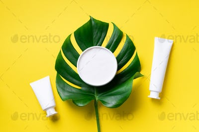 White plastic cosmetic jar, tube, bottle and tropical monstera leaf over yellow background. Top view