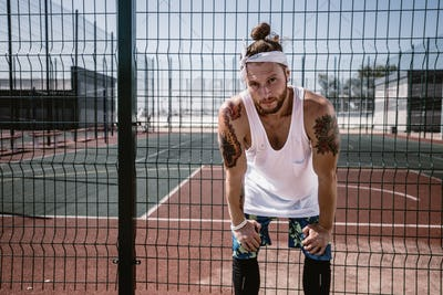 Young man with white headband on his head and tattoos on his arms dressed in the white t-shirt