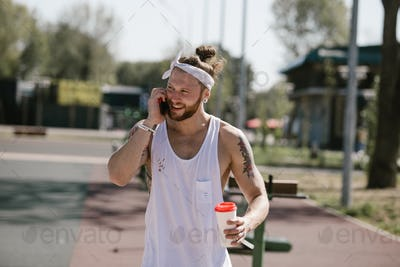 Young man with white headband dressed in a white t-shirt talked by phone and holds a plastic cup in