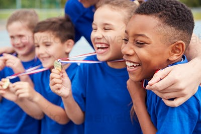 Children With Male Coach Showing Off Winners Medals On Sports Day