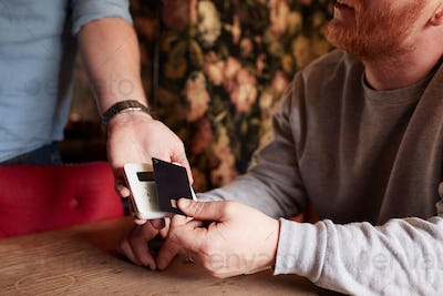 Close Up Of Customer Paying In Hotel Restaurant Using Contactless Card Reader