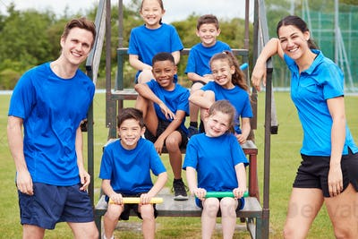 Portrait Of Children With Male And Female Coaches Preparing For Relay Race On Sports Day
