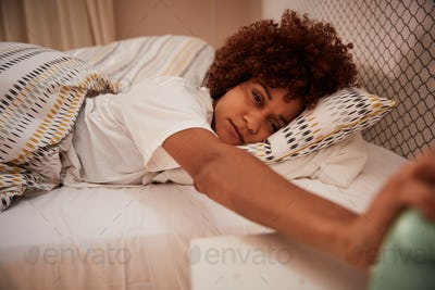 Millennial African American woman half asleep in bed, reaching out to stop alarm clock, close up