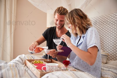 Millennial white couple celebrating with champagne,  breakfast and gifts in bed, close up