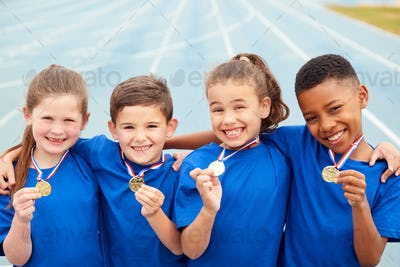 Portrait Of Children Showing Off Winners Medals On Sports Day