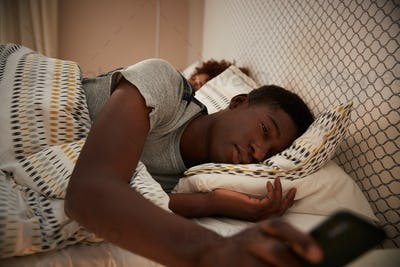Millennial African American man half asleep in bed holding smartphone