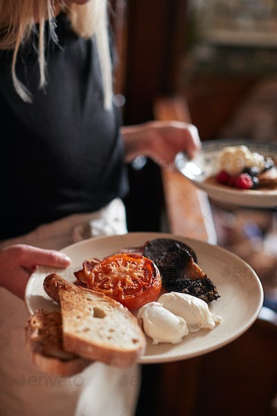 Close Up Of Waitress Working In Traditional English Pub Serving Breakfast To Guests