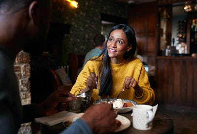 Couple At Table In Traditional English Pub Eating Breakfast