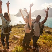 Millennial friends on a hiking trip celebrate reaching the summit, cheering with arms in the air