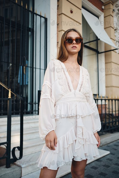 Young stylish girl in sunglasses and beautiful white dress looking in camera on cozy city street