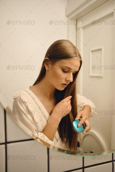Young romantic girl in white dress dreamily brushing her hair in front of the mirror