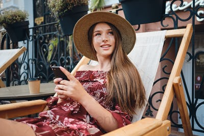 Beautiful girl in dress and straw hat holding cellphone dreamily looking aside in street cafe