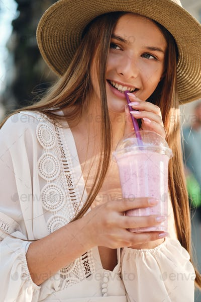 Attractive smiling girl in white dress and hat drinking smoothie happily on cozy city street